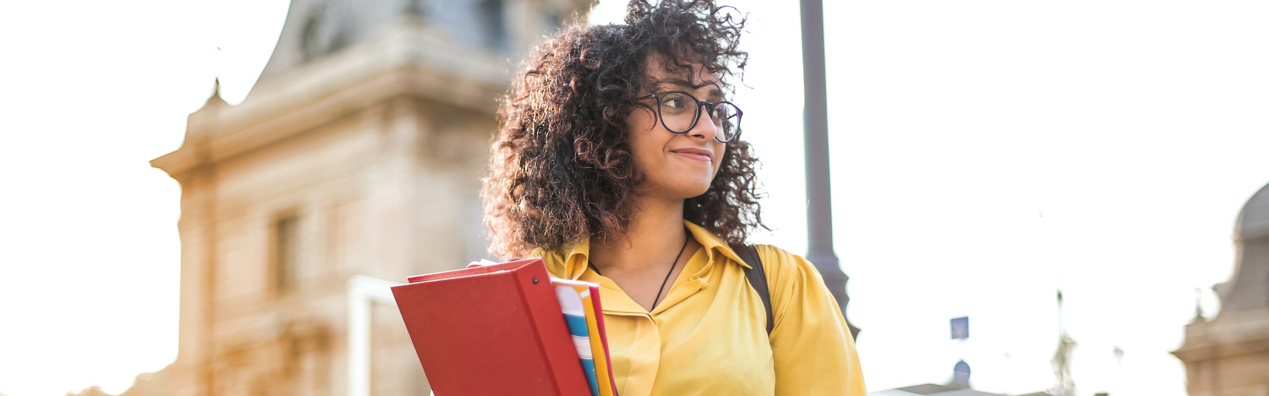 Header image of a Black girl with glasses holding several books